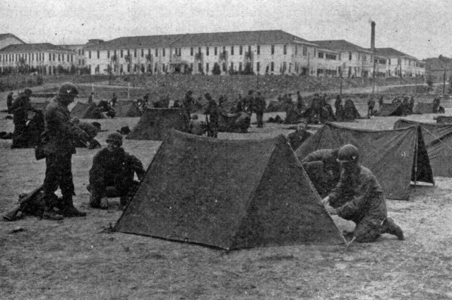 In the course of military training, Soldiers in Kyushu practice tent pitching. In the background is a portion of the camp area.