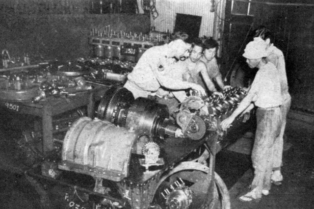 A noncommissioned officer supervises the assembly of marine engines by Japanese factory hands.