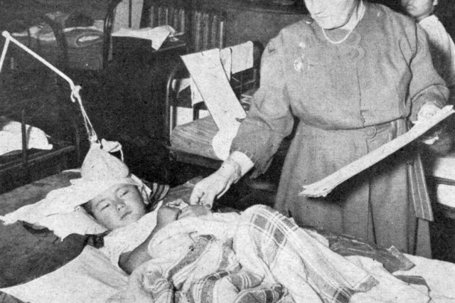 A doctor of the Tokyo Military Government team checks the pulse of a young encephalitis victim.