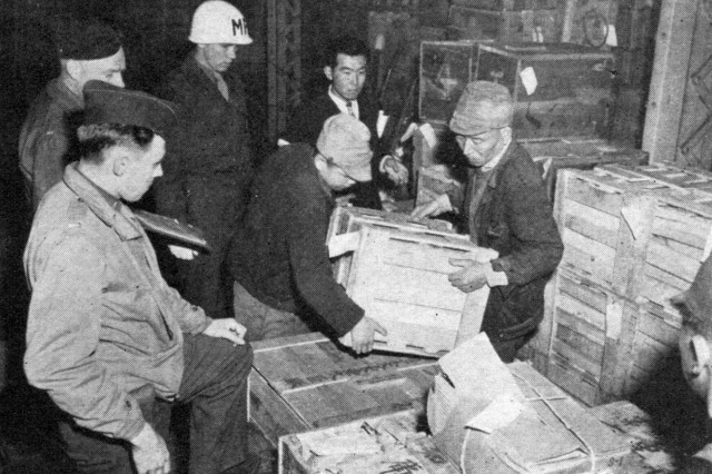 Military personnel supervise the loading of narcotics by Japanese laborers. The narcotics--unfit for medical purposes--will be burned to prevent their misuse.