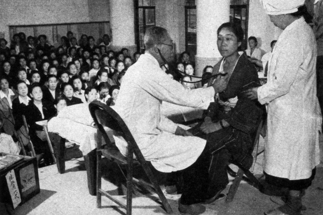 For the instruction of midwives, a Red Cross hospital director demonstrates the type of physical examination given to maternity patients.