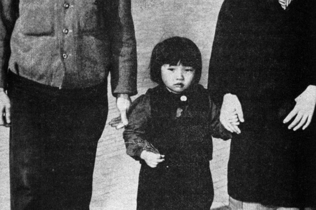 Personal liberties in the new Japan are symbolized by this Japanese family. The wife walks beside her husband instead of behind.