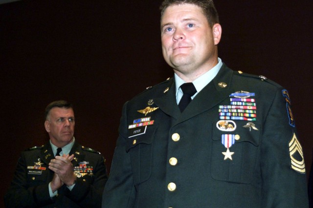 Master Sgt. Anthony S. Pryor (right) of the 5th Special Forces Group looks on as he is applauded by 5th SFG commander Col. John Mulholland after receiving the Silver Star Medal during a June 12 ceremony at Fort Campbell, Ky. Pryor was awarded the Silver Star for his gallantry in combat during a January 2002 raid on a suspected al Qaeda stronghold in Afghanistan, when he single-handedly eliminated four enemy soldiers, including one in unarmed combat, all while under intense automatic weapons fire and with a crippling injury.