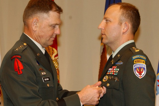 Maj. Mark Mitchell is pinned Nov. 14 with the Distinguished Service Cross, for combat actions in Operation Enduring Freedom, by Gen. Bryan Brown, commander, U.S. Special Operations Command.