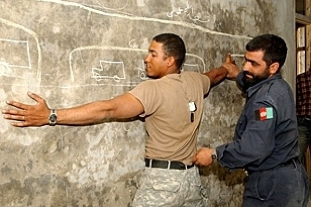 U.S. Army Sgt. Michael Mitchell searches a fellow soldier, U.S. Army Sgt. Scott Greene, as Afghan National Police officers observe at an Afghan National Army outpost in the Kohi Sofi District about 40 kilometers south of Bagram, Afghanistan, June 3, 2006