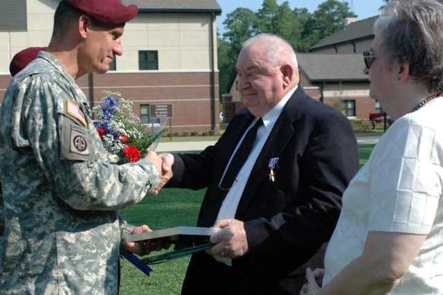 Retired Sgt. 1st Class Richard L. Smith shakes hands with 82nd Airborne Division Commanding General Maj. Gen. David Rodriguez after accepting the Silver Star and being inducted as an honorary member of the 82nd Aviation Regimental Association Aug. 29 for his contributions during the battle at Ia Drang Valley in Vietnam.