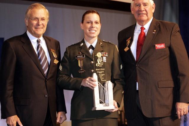 "Sgt. Renee Kraus receives the ""Spirit of Service Award"" from American Legion National Commander Thomas Bock and Secretary of Defense Donald Rumsfeld."