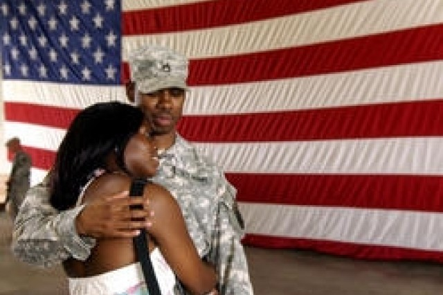 Staff Sgt. Kwesi Morgan holds his wife Ykeia Morgan close Sunday afternoon after returning from a year-long deployment.