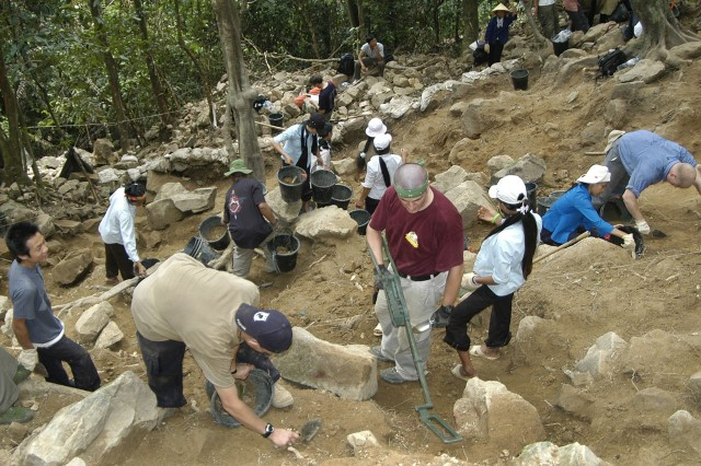Members of the Joint POW/MIA Accounting Command and local villagers work together excavating a crash site in Dong Hoi, Vietnam, July 16, 2006. A 15-member JPAC team including a forensic anthropologist, life support investigator, explosive ordnance disposal technician and field medic, deployed from Hickam Air Force Base, Hawaii, worked in Vietnam for a month attempting to recover the remains of pilots that crashed in the area during the Vietnam War.
