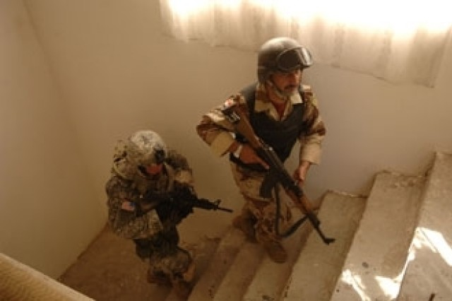 U.S. Army Sgt. Partyka (left) and an Iraqi army soldier climb a flight of stairs as they conduct a combined cordon and search mission in Baghdad Sept. 10. Photo by Master Sgt. Mike Buytas.