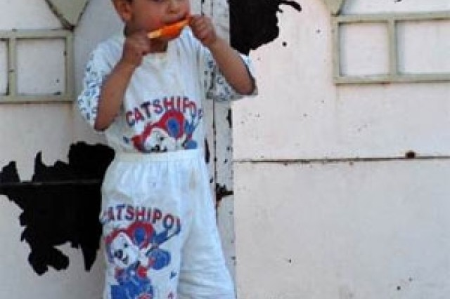 A Kurdish Iraqi boy eats a popsicle outside in Dohuk. Department of Defense photo by Jim Gordon.