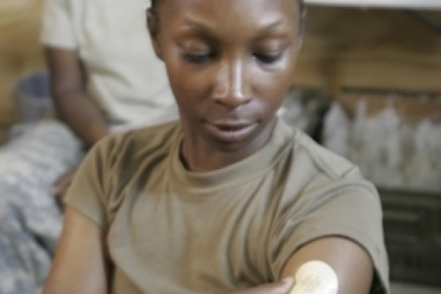 SGT Keeouka Williams from the 2nd Brigade Combat Team, 101st Air Assault Division, puts on a nicotine patch to help her quit smoking. Williams is participating in a smoking cessation program at Camp Striker, near Baghdad.