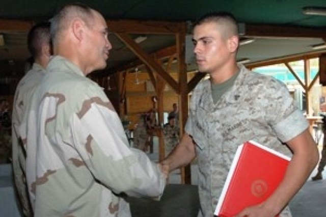 Camp Lemonier, Djibouti (September 6, 2006) (Right) Lance Cpl. Joasseht Ramos, from Mexico, is congratulated by Rear Adm. Richard W. Hunt, Commander, Combined Joint Task Force - Horn of Africa, after becoming a U.S. citizen. Ramos and 19 other service members took the oath of allegiance, at Camp Lemonier, Djibouti, during their first Military Naturalization ceremony.