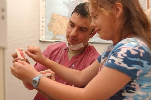 Capt. José Cangas, one of four dentists participating in this year's Advanced Program in General Dentistry-One Year, watches as Sophia Haley, 10, a Landstuhl and Middle School sixth grader, shows how she flosses her teeth Aug. 25 at the Pulaski Dental Clinic on Pulaski Barracks in Kaiserslautern.<br/>