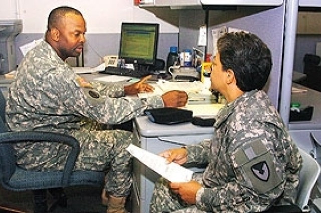 Sgt. 1st Class Bryan Barrett processes paperwork for Lt. Col. Carmen Figueroa, Headquarters Army Materiel Command.
