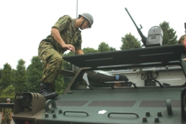 Sgt. Akira Hasegawa from Japan Ground Self Defense Force gives instruction to 1st Lt. Ann Teragawa, S-1 of the 78th Signal Battalion about the NBC recon vehicle Aug. 25 during a visit to the JGSDF 101st Chemical Defense Unit at Camp Omiya in the Saitama Pref.