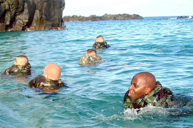 Sgt. 1st Class Eric Powell (right) uses the pants of his battle dress uniform as a flotation device during 2nd Brigade Combat Team water survival training at Waimea Bay, Hawaii. This photo appeared on www.army.mil.