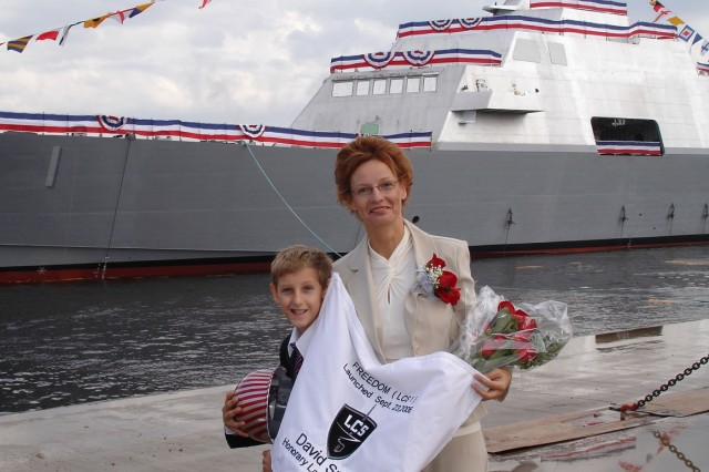 "Birgit Smith, widow of Medal of Honor recipient Sgt. 1st Class Paul R. Smith, and her son David pose just moments after the 377-foot, 40-knot, Navy ship ""Freedom"" was launched Sept. 24. Smith is the sponsor of the littoral combat ship. """