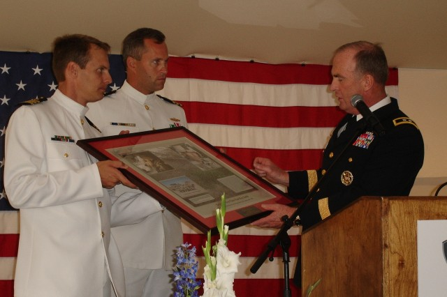 Maj. Gen. Rick Lynch, commander of the 3rd Infantry Division and Fort Stewart, presents a gift in honor of Medal of Honor recipient, Sgt. 1st Class Paul R. Smith to the prospective commanding officers of the future-USS Freedom, Commanders Michael Doran and Donald Gabrielson for placement on the new ship.""