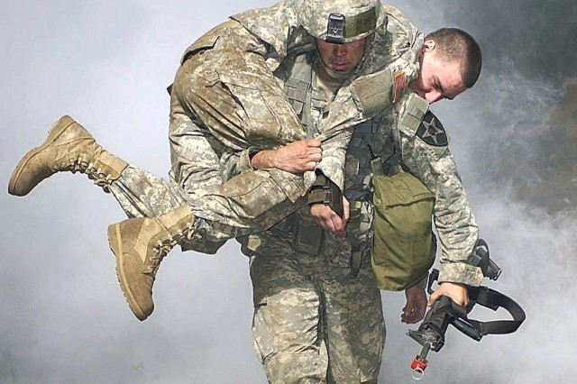 """Capt. Charles Moore, a company commander from the 2nd Infantry Division, carries a """"casualty"""" during the nuclear, biological and chemical portion of the Expert Field Medical Badge training at Fort Lewis, Wash."""