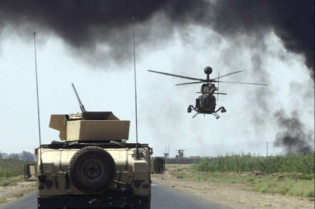 Soldiers from the 25th Infantry Division and a Kiowa helicopter move past an oil fire during a convoy to Al Jawala, Iraq.