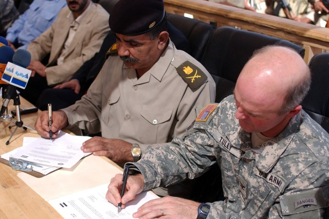 Maj. Gen. Hussein Al Ghazali (left), commander, 5th Regional Department of Border Enforcement, and Col. John Tully, commander, 2nd Brigade Combat Team, 4th Infantry Division, sign documents officially transferring responsibility of Forward Operating Base Duke from Multi-National Division - Baghdad to Iraqi security forces Oct. 2 at FOB Duke in the Najaf province. In one year, the ISF have gone from operational control of 11 forward operating bases to the present-day total of 51.