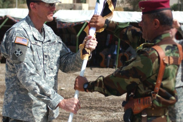 Col. Brian Jones, left, commander, 3rd Heavy Brigade Combat Team, 4th Infantry Division, passes the Iraqi colors to Gen. Rahman Jerry Challab, commander, 3rd Brigade, 5th Iraqi Army Division, signifying the 3rd Bde.'s assumption of command of the northern portion of Diyala Province. The area used to be under the command of the 3rd HBCTs 2nd Squadron, 9th Cavalry.