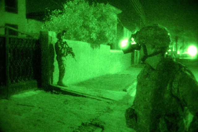 Col. Michael Beech, commander, 4th Brigade Combat Team, 4th Infantry Division, makes assessments while Sgt. Jeffrey Rogers, command personal security detachment team leader, pulls security during a mission with a platoon from the 2nd Battalion, 506th Regimental Combat Team, 101st Airborne Division.