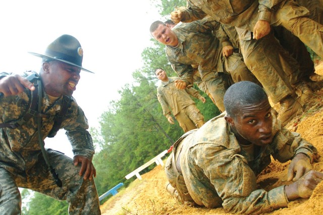 Sgt. Primus Brown, a drill sergeant, and recruits offer words of encouragement to a trainee negotiating the obstacle course at Fort Benning, Ga. This photo appeared on www.army.mil.