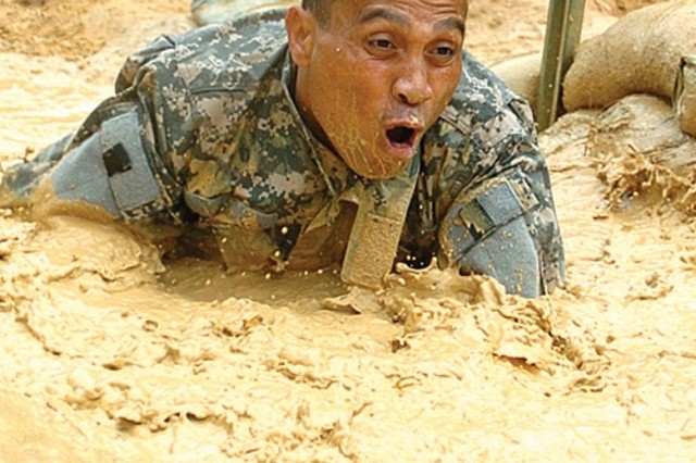 Pvt. Charlie Lonno crawls through a Basic Training obstacle course at Fort Benning, Ga.