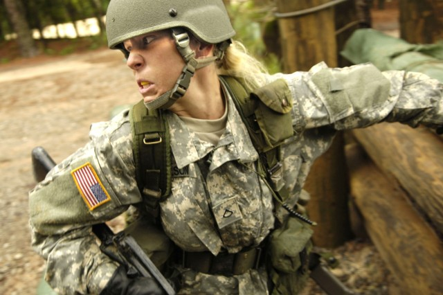 A Soldier trainee negotiates a log obstacle on the confidence course during her 9-week basic training program at Fort Jackson, S.C.