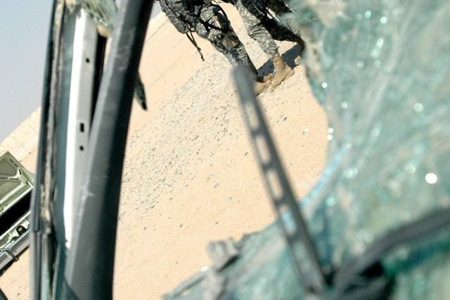 Soldiers prepare to enter a room, near the broken glass of a destroyed vehicle, during MOUT training, October 18, 2006.