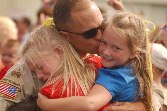 A Soldier is welcomed home by family members
