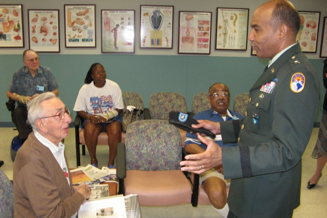 Brig. Gen. Nolen Bivens, U.S. Southern Command chief of staff, talks to a Veterans Administration Hospital patient while others look on during a visit Oct. 26. Leaders from SOUTHCOM visit the hospital monthly to talk with patients and hospital staff.