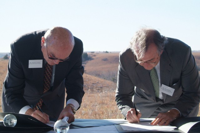 Merlyn Carlson, under secretary of agriculture for Natural Resources and Environment (left) and Alex Beehler, assistant deputy under secretary of defense for Environment, Safety and Occupational Health, sign an agreement making USDA's Natural Resource Conservation Service a partner in DoD's Readiness and Environmental Protection Initiative conservation buffer program in a Nov. 8 ceremony at Fort Riley, Kan. The agreement will help protect land around military bases from incompatible development nearby.