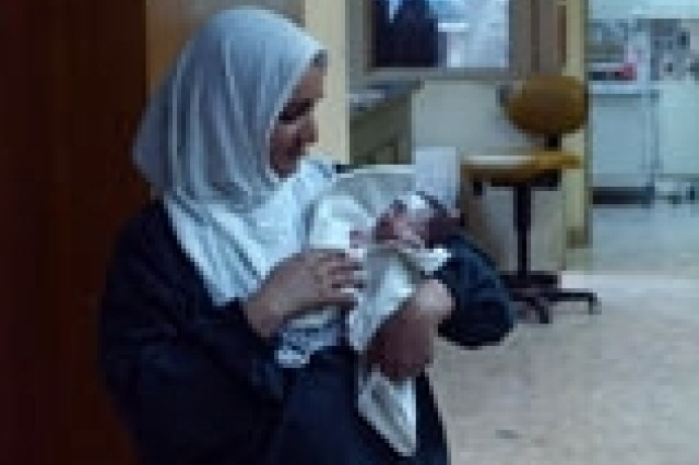 A prematurely-born Iraqi infant is held by a nurse at Baghdad Teaching Hospital.