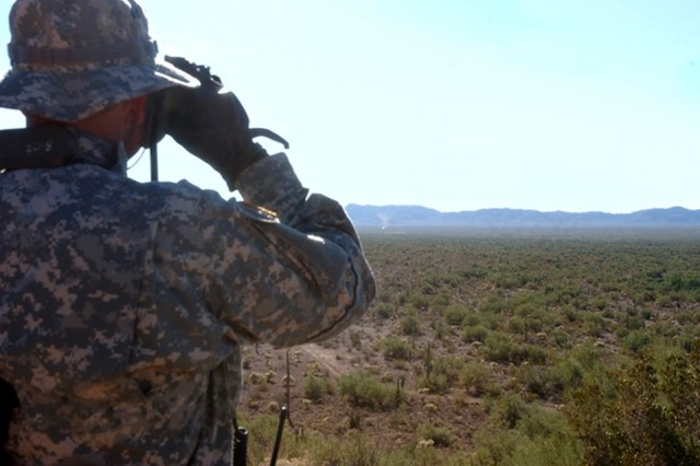 "Indiana National Guard Sgt. Brian Clevenger follows a ""dust devil"" that might be a vehicle through his binoculars while assisting Tucson Sector Border Patrol Agents at an observation post in southern Arizona."