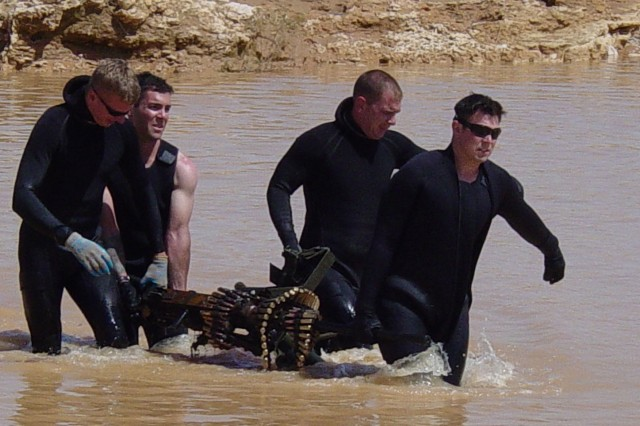 (Left to right) Spc. Brian Myers, Staff Sgt. Kurt Langely, Staff Sgt. Eric Shultz and Sgt. David Gills - all divers with the 544th Engineer Team currently based in Kuwait - do some heavy lifting.