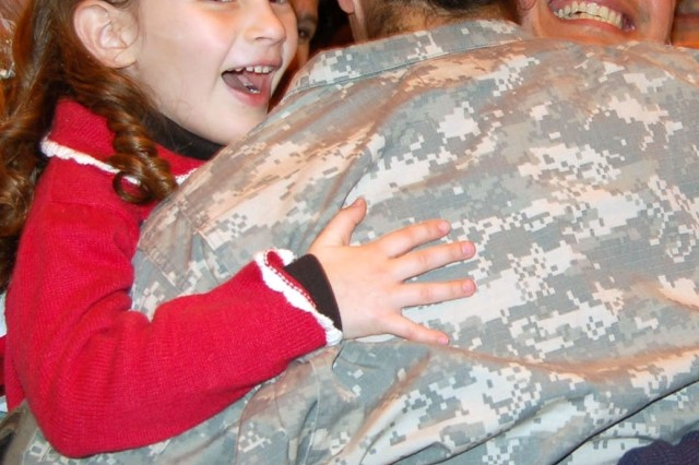 """1st Lt. Rosanna Vasquez Brown hugs her brother, Capt. Martin Vasquez, and her daughter, Elisa at Campbell Army Airfield. Over the last five years, either Rosanna; her husband; her brother, Staff Sgt. Francisco Vasquez (not pictured); and her other brother Martin have been either been deployed or away on a training mission so they could not meet together as one family. At one point, a 10-minute helicopter ride separated Rosanna from her husband and brother, Francisco. """"When the rest of us have been able to get together, someone is always missing from the picture,"""" Francisco said. Francisco, now stationed at Fort Campbell, returned last month from Iraq, where he served as a flight medic. He flew over 300 combat hours and was responsible for the care and safety of more than 700 patients. Brother Martin served in Afghanistan and Uzbekistan. He was awarded the Bronze Star Medal."""