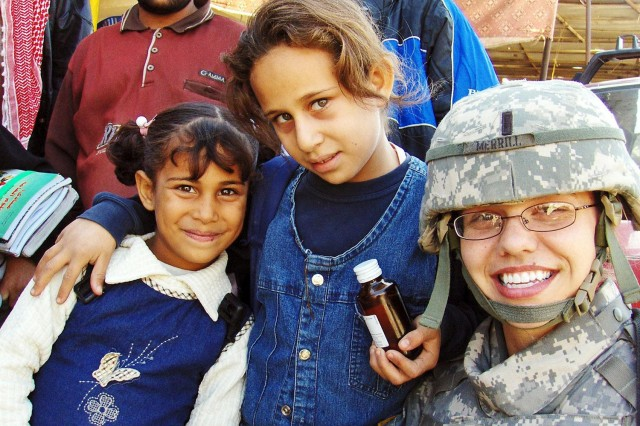 1st Lt. Serena Merrill, from the 2nd Brigade Combat Team, 10th Mountain Division, meets Iraqi children during a visit to the Yusufiyah marketplace.
