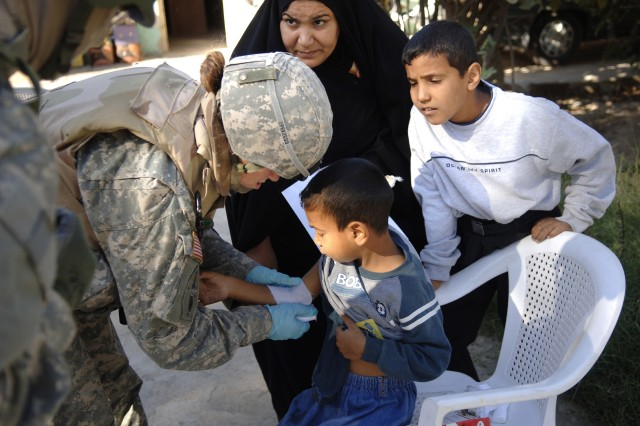 A medic with the 172nd Stryker Brigade Combat Team cleans an Iraqi child's wound during a medical and humanitarian mission in Baghdad Nov. 9. The unit is preparing to return to Alaska in December after 16 consecutive months of operations there.