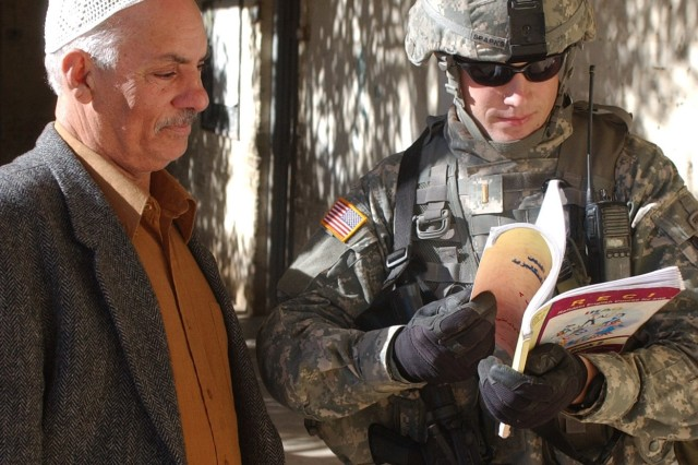 2nd Lt. Joseph Sparks reads a math textbook with a teacher at Kahnarbat Primary School in Al Alabara, Iraq, during a visit designed to help Soldiers develop relationships with local residents. Sparks is from the 12th Infantry Regiment, 1st Cavalry Division.