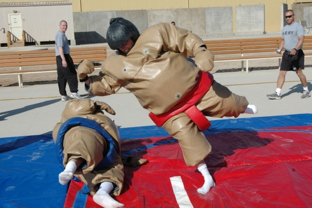 """Spc. Nathaniel Jones jumps to slam Spc. Juan Garcia during a sumo wrestling match Nov. 26. Soldiers from Company B, 215th Brigade Support Battalion, 3rd """"Grey Wolf"""" Brigade Combat Team, 1st Cavalry Division, enjoyed a well-deserved day of fun and relaxation at Forward Operating Base Warhorse, Baqubah, Iraq."""