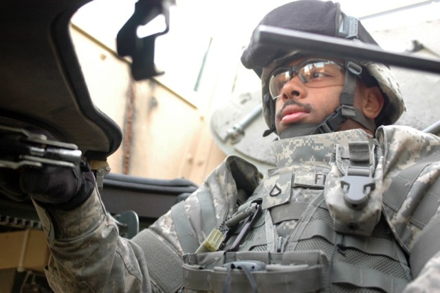 Pfc. David Fielder mans the gunner's turret during a trip through the al Doura District of Baghdad Nov. 20. Fielder and the rest of his fellow troops from Company A, 2nd Battalion, 12th Infantry Regiment, 2nd Brigade Combat Team, 2nd Infantry Division, have been patrolling the dangerous section of the capital city in hopes of brining security to local residents.