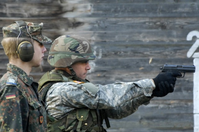 A German Army weapons instructor assists a U.S. Army, Europe Soldier on a range in Wieden, Germany. Soldiers from both countries fired each other's weapons. The U.S. Soldiers used the MG-3 machine gun and P-8 pistol, while their German counterparts trained on the M-4 carbine.