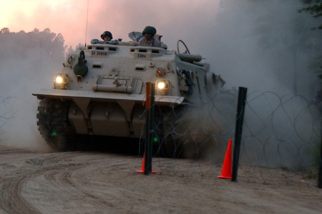 Soldiers speed through a checkpoint in a recovery vehicle from 1st Brigade, 3rd Infantry Division while under simulated insurgent fire during a mission readiness exercise at Fort Stewart, Ga.