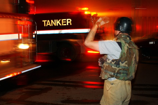 Firefighters assigned to Station #1 North and Station #2 South of Victory Fire Department arrive to put out a fire, assess damage, and find a projectile after a 244 mm rocket hit the Camp Victory base complex in Baghdad, Iraq, Nov. 15, 2006.