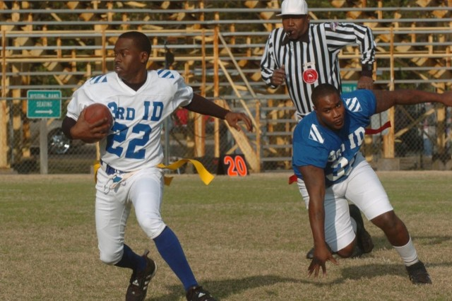 """A player from B Company, 603rd Aviation Support Battalion's """"Killer Bees"""" outmaneuvers the defense from Company A, 703rd Brigade Support Battalion's """"Hitmen"""" to run the ball down the field during the Marne Bowl Flag Football Championship game Nov. 20 in Hinesville, Ga. The """"Hitmen"""" eventually triumphed, 32-18, to claim the intramural championship title during the 3rd Infantry Division's Marne Week celebration."""
