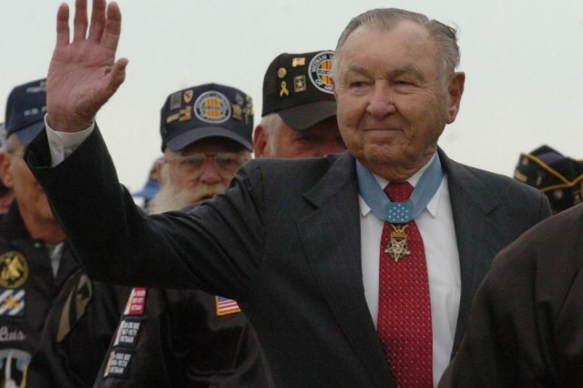 Retired Col. Charles P. Murray, a 3rd Infantry Division World War II veteran and Medal of Honor recipient, waves to the crowd as he and other veterans march across Cottrell Field during the Pass in Review ceremony Nov. 21.