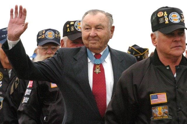 Retired Col. Charles P. Murray, a 3rd Infantry Division World War II veteran and Medal of Honor recipient, waves to the crowd as he and other veterans march across Cottrell Field, Fort Stewart, Ga., during the pass in review ceremony Nov. 21.
